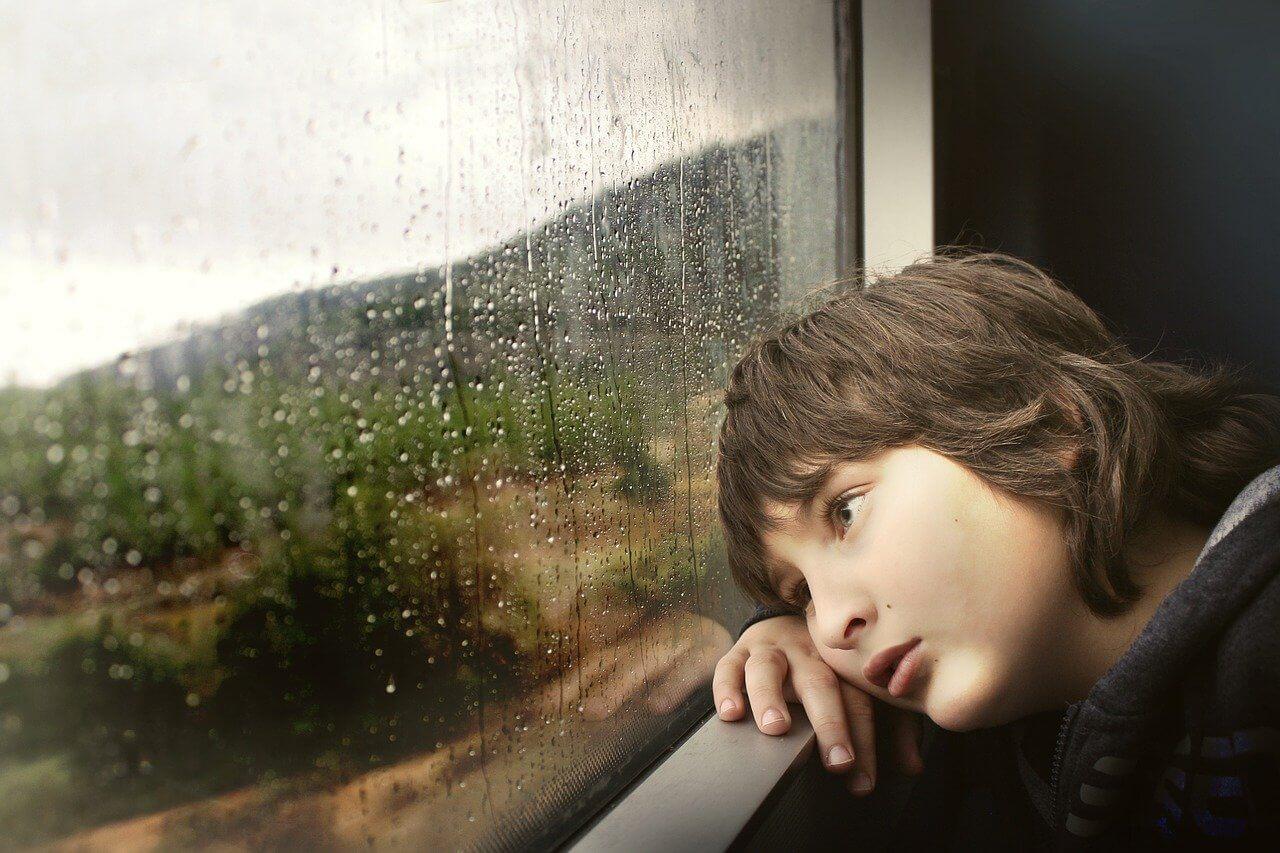 雨の日に窓の外を見つめる子供